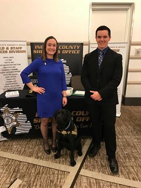Rachel Striks and Eric Nesbitt standing in front of the Ingham County Sheriff's Office booth at the 2019 Criminal Justice Career Fair